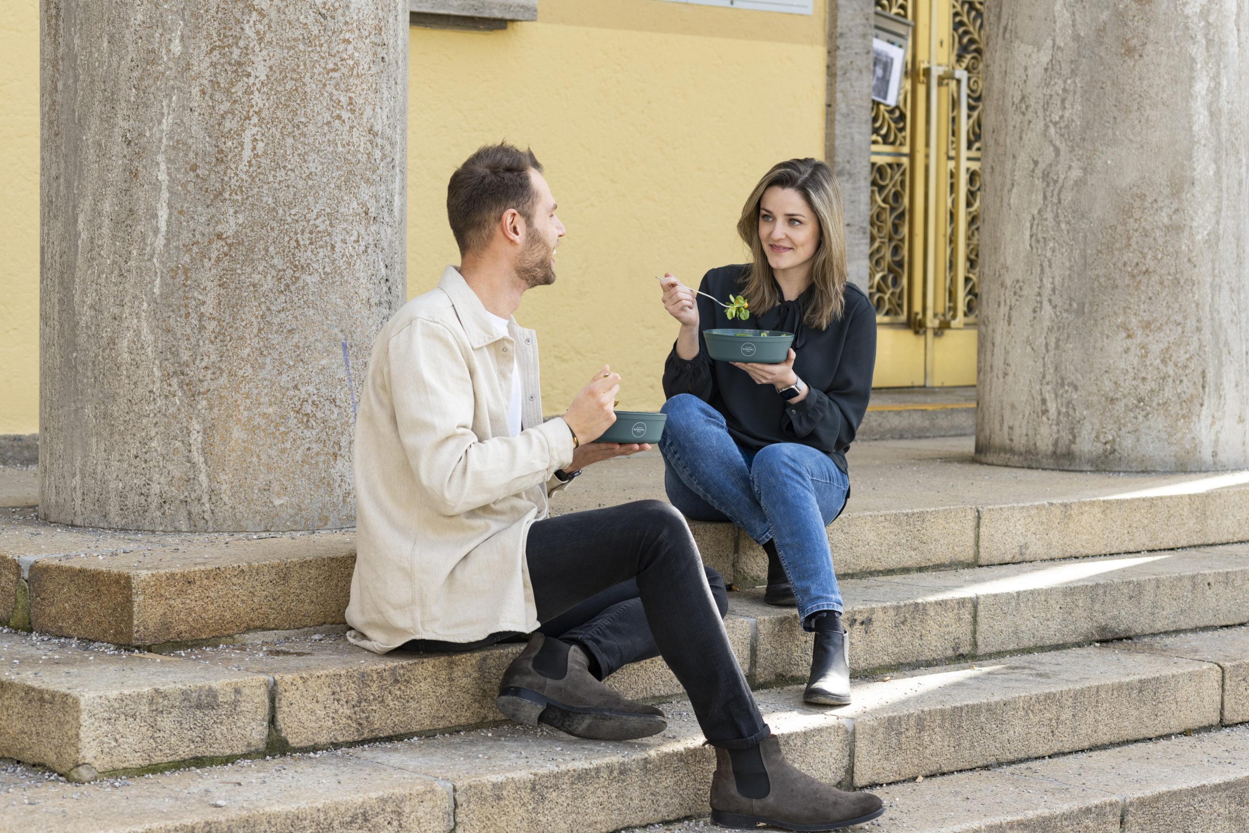 Man und Frau essen aus REBOWL und sitzen auf Treppenstufen
