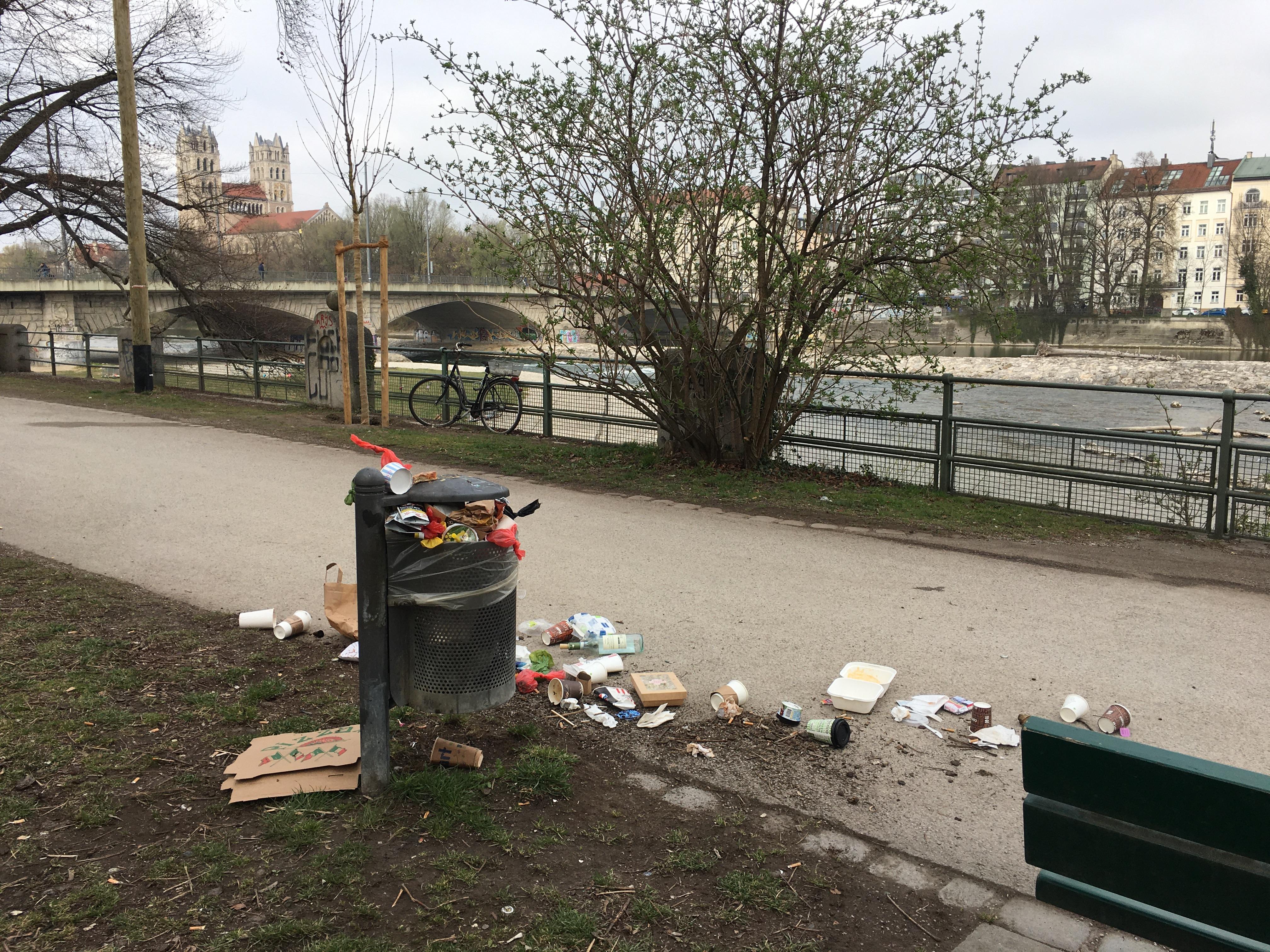 Überquellender Mülleimer mit Pappbechern mit Deckel und weiteren Einweg-Verpackungen drumherum an der Isar in München